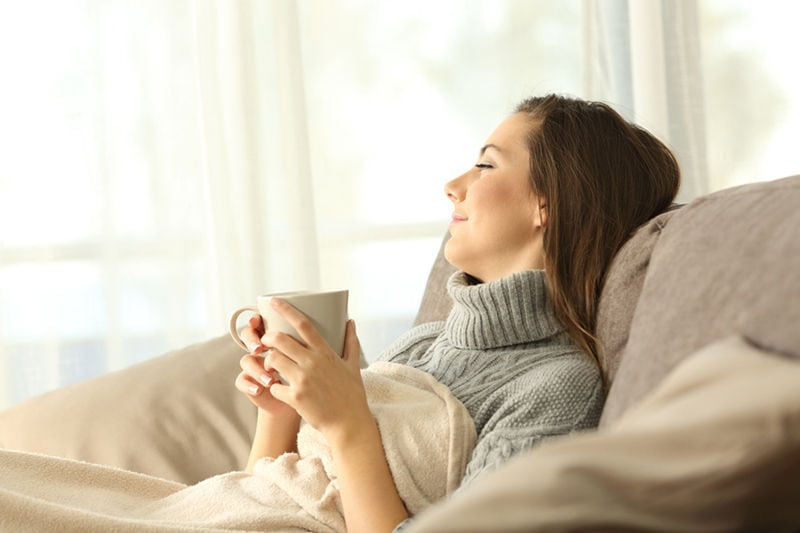 Portrait of a pensive woman relaxing sitting on a sofa in the living room in a house