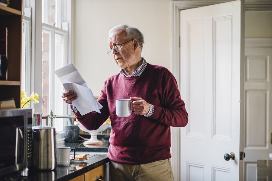 Senior man is standing in the kitchen of his home with bills in one hand and a cup of tea in the other. He has a worried expression on his face.
